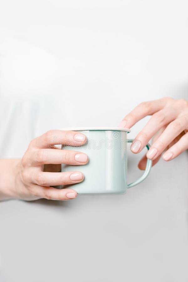 Beautiful female hands holding an enamel cup. Manicure with nude nail polish. Copy space royalty free stock photo