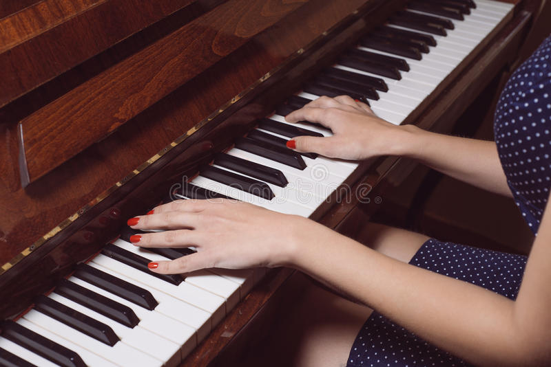 Beautiful female hands on the keys of an old piano stock photography