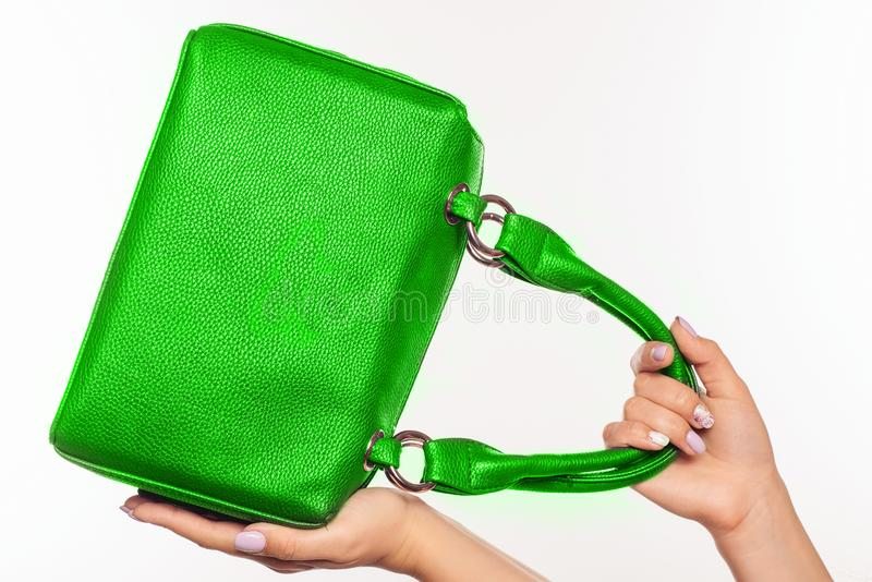 Beautiful female hands with manicure hold an green handbag royalty free stock photography