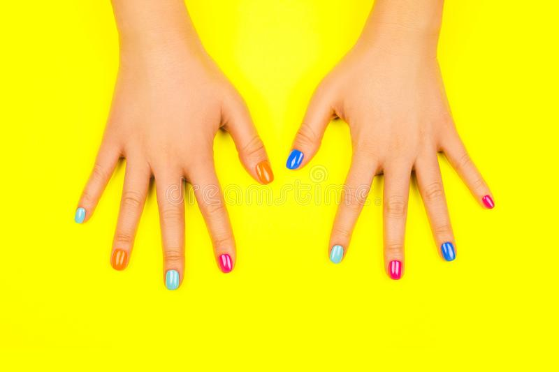 Beautiful female hands with manicure in trendy neon colors on yellow background. Beautiful female hands with manicure in trendy neon colors on bright yellow stock image