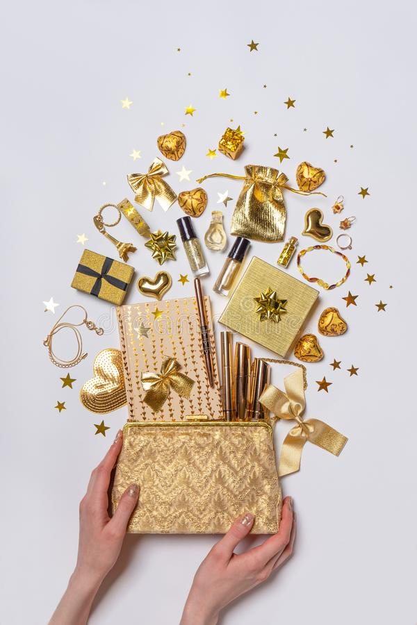 Beautiful female hands and stylish bag with feminine accessories, cosmetics, jewellery, gifts and decorative items in golden royalty free stock photography