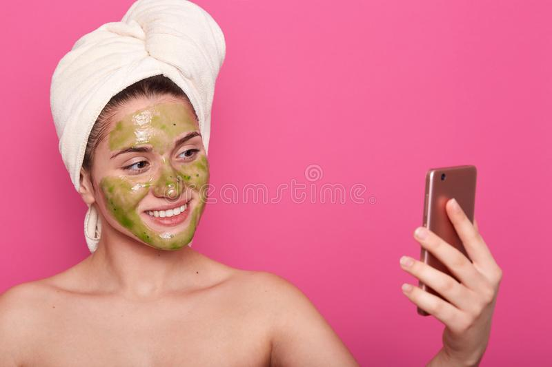 Beautiful female having green mask on face, wrapped white towel, poses half naked, taking selfie on smartphone in bathroom, posing royalty free stock image