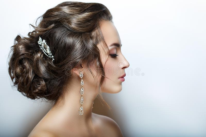 Beautiful female head. Profile. Closeup portrait of. Perfect skin, beautiful hair and makeup. Large and bright decorations. royalty free stock photo