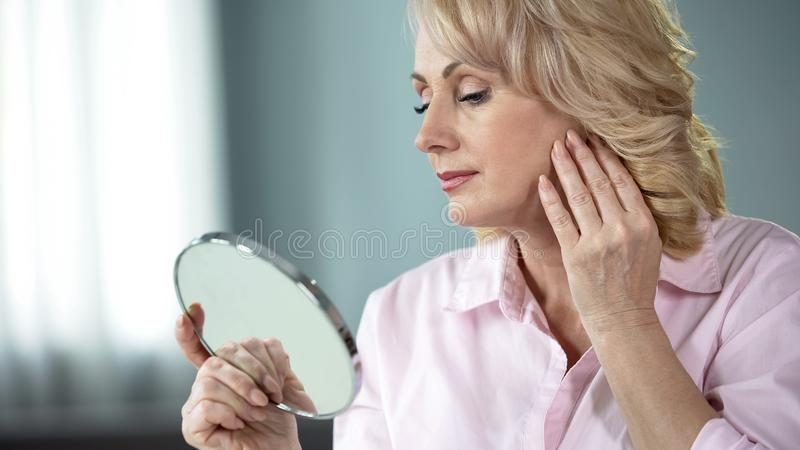Beautiful female in her 50s looking at face skin mirror, collagen cream effect. Stock photo royalty free stock photos
