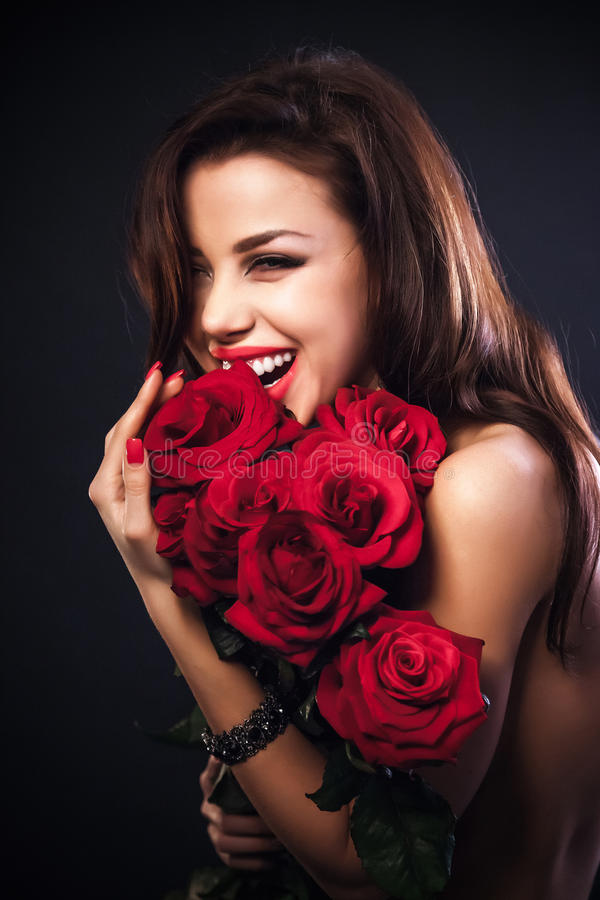 Beautiful female holding red roses bouquet, valentines day. Stylish beautiful young woman holding red roses bouquet, tender flowers in hands, brunette female royalty free stock photography