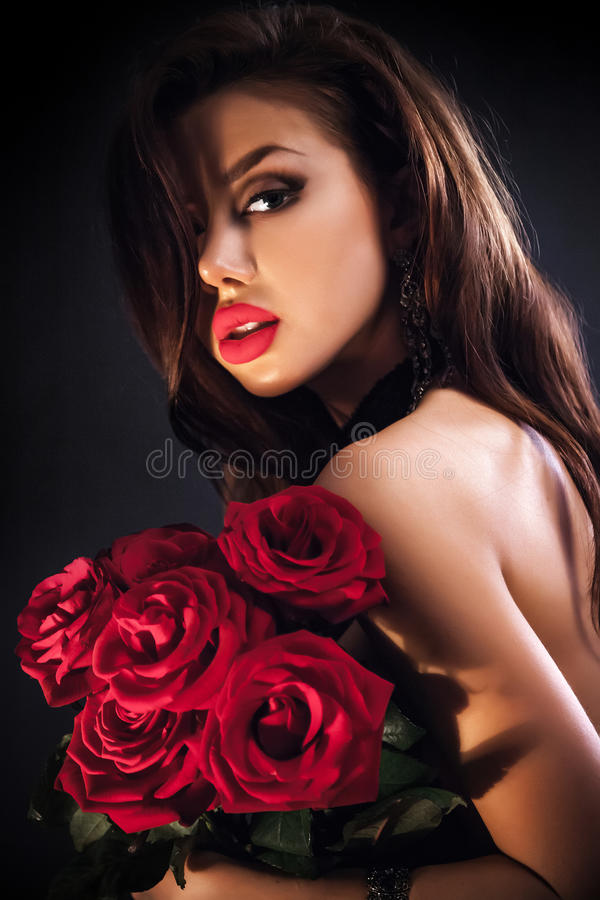 Beautiful female holding red roses bouquet, valentines day. royalty free stock photo