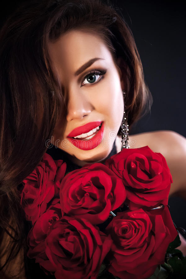 Beautiful female holding red roses bouquet, valentines day. Stylish beautiful young woman holding red roses bouquet, tender flowers in hands, brunette female stock photos