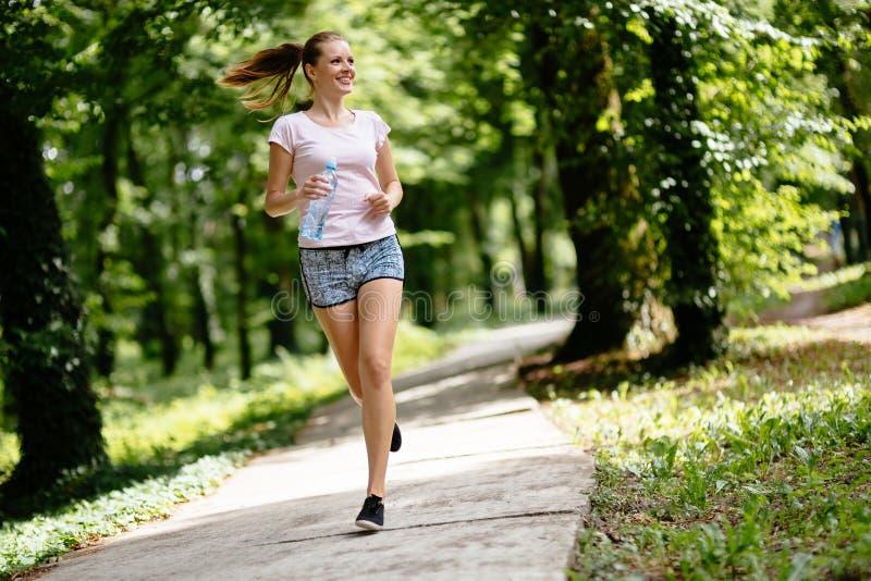 Beautiful female jogger in nature. Beautiful athletic female jogger in nature stock images