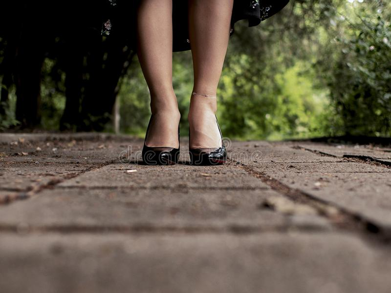 Beautiful female legs in black patent-leather shoes on outdoor tiles stock images