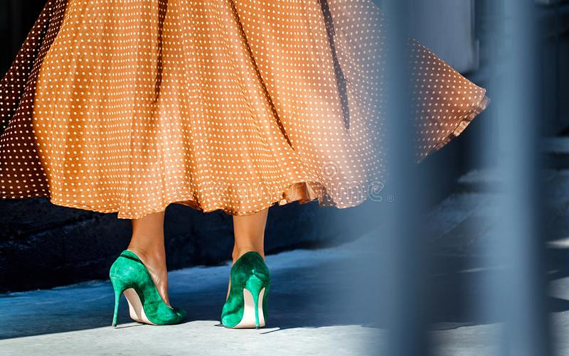 Beautiful female legs in high heel shoes. close-up. green suede pumps. Girl dancing and spinning in a magnificent dress. stock photography