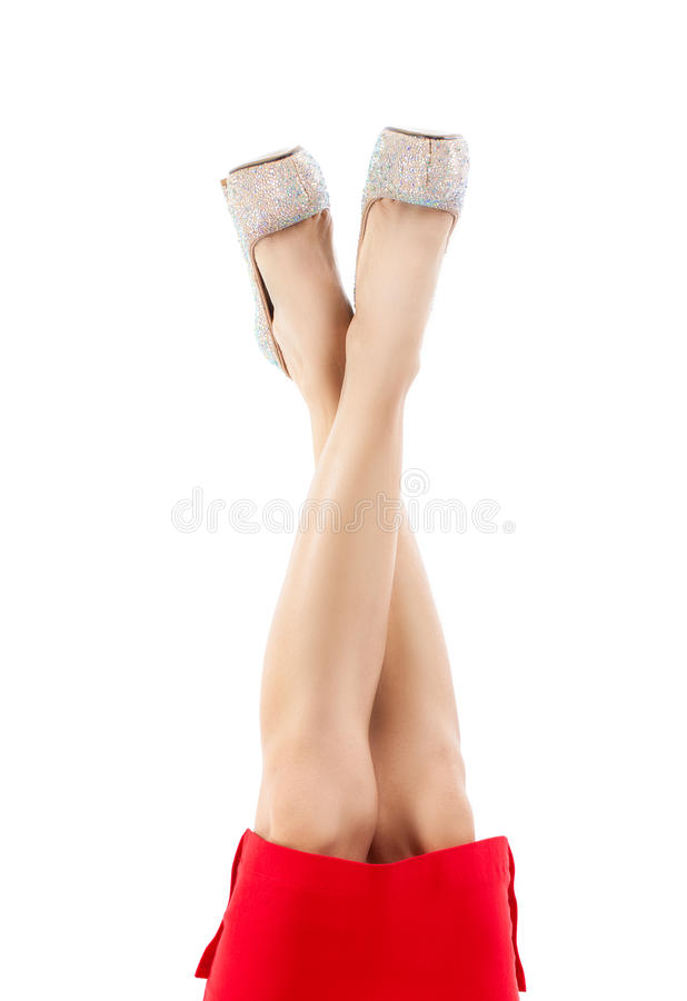 Beautiful female legs in light shoes with rhinestones. Slender legs, high heels, bright sparkling crystals stock photography