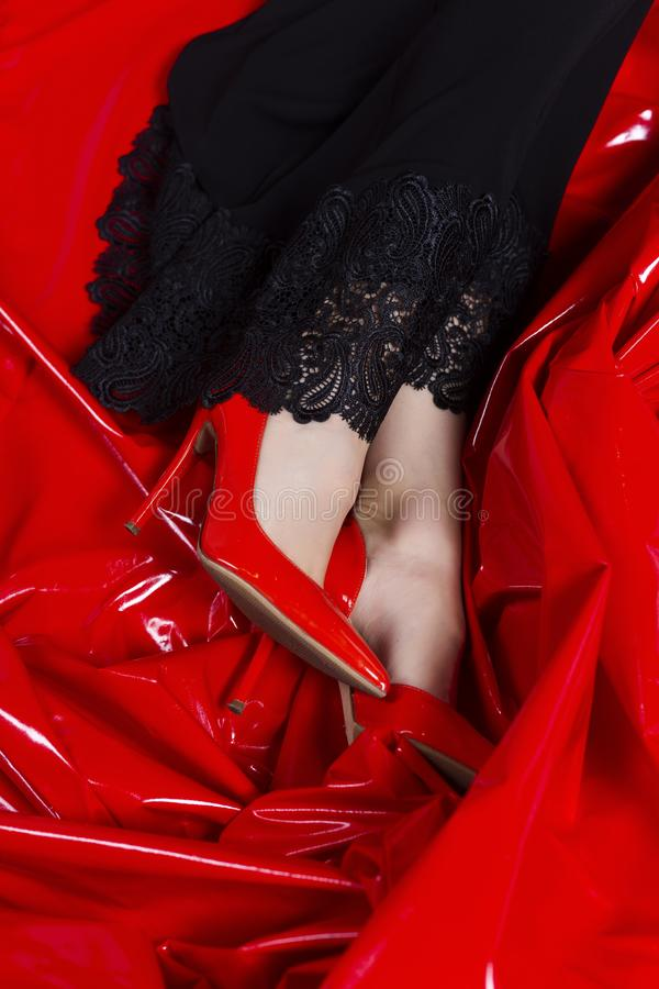 Beautiful female legs in red shoes and black dress with lace on the background of latex red fabric. Conceptual, advertising and stock photography