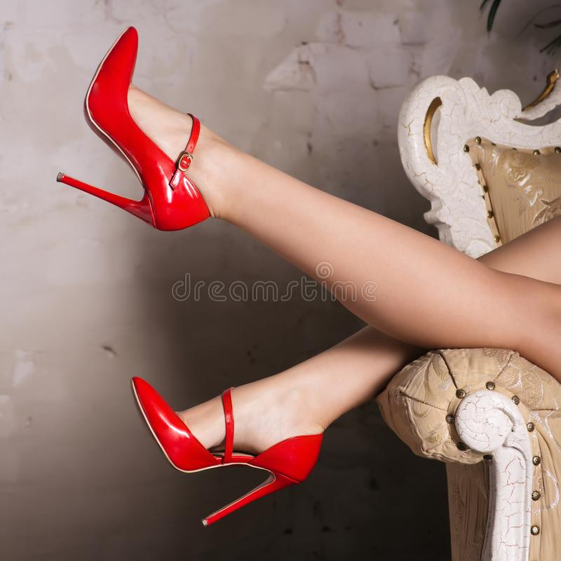 Beautiful female legs in red stylish high-heeled shoes are lying on the chair royalty free stock photos