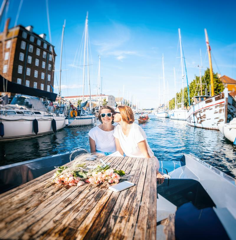 A beautiful female lesbian couple in white dresses on a boat, a. Wedding in Denmark, Copenhagen, Happiness, freedom and equal rights for LGBT couples royalty free stock image