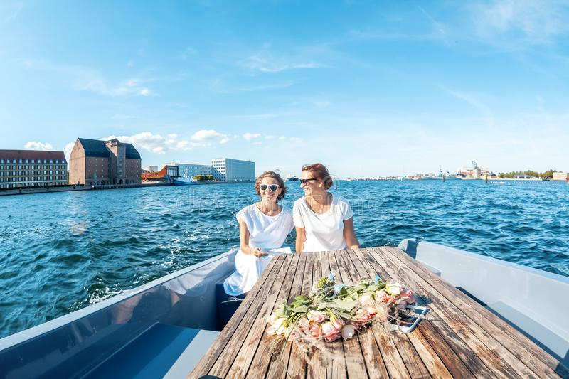 A beautiful female lesbian couple in white dresses on a boat, a stock photo