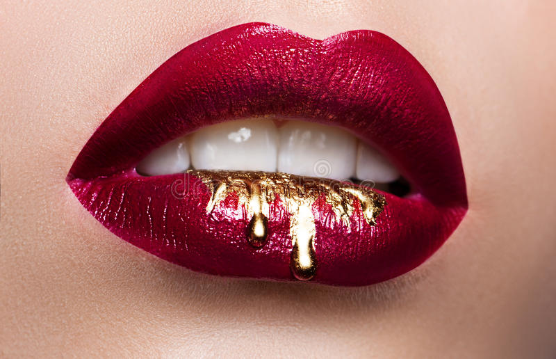 Beautiful female lips closeup. Red lipstick, gold paint flowing over his lips. Stock Photo. Cosmetic Advertising stock photos