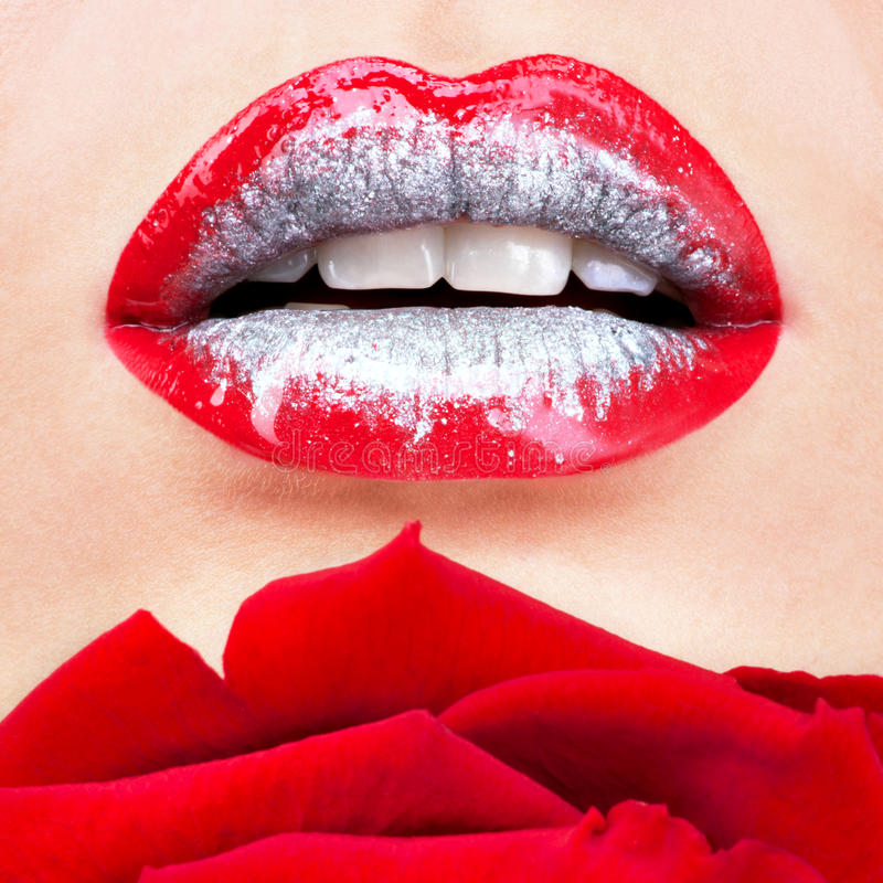 Beautiful female lips with shiny lipstick and red rose. Closeup beautiful female lips with shiny red gloss lipstick and rose stock photography