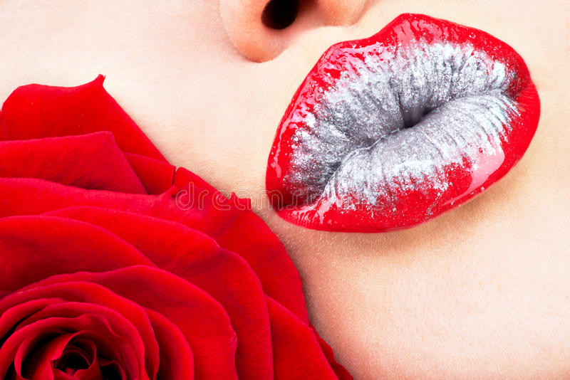 Beautiful female lips with shiny lipstick and red rose. Closeup beautiful female lips with shiny red gloss lipstick and rose stock photos