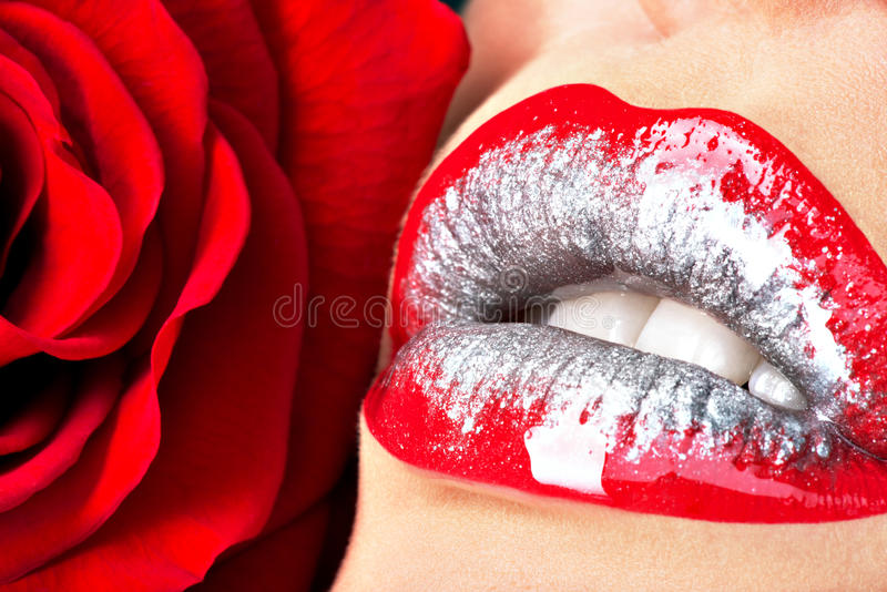 Beautiful female lips with shiny lipstick and red rose. Closeup beautiful female lips with shiny red gloss lipstick and rose royalty free stock images