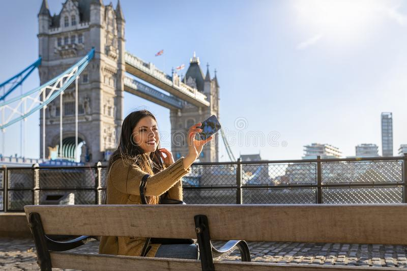 Female London traveler takes a selfie picture in front of the Tower Bridge stock photography