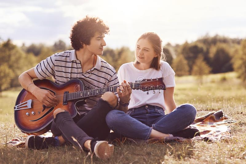 Beautiful female looks with love and happiness at her boyfriend who plays guitar and sings romantic songs to lover, have unforgett. Able date outdoor, enjoy stock photos