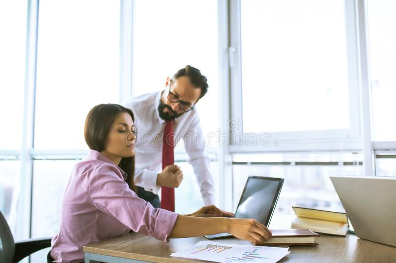 Business people planning strategy analysis. Beautiful female manager and team lead discussing data on laptop. Office concept stock photography