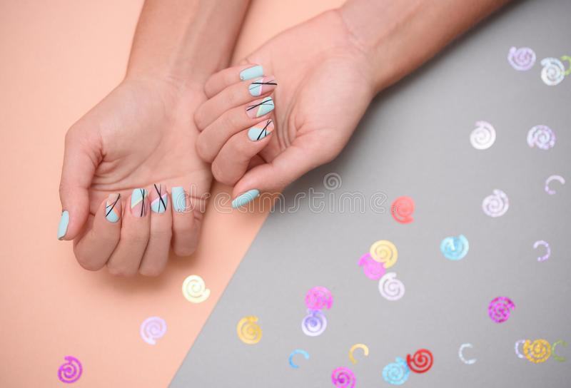 Beautiful female manicure on bed background with sparkles stock photo