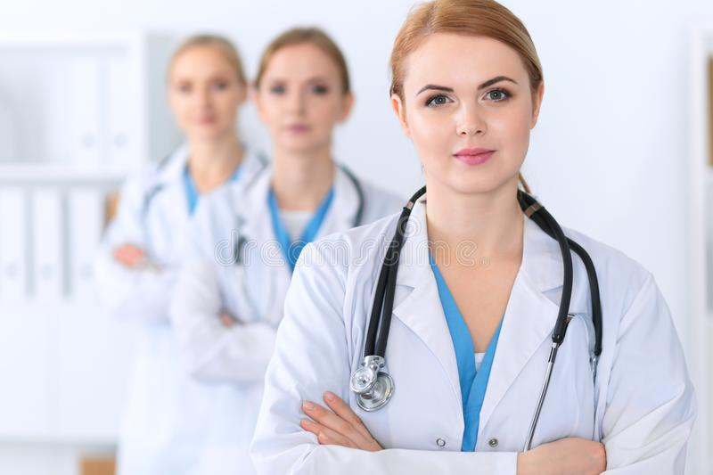 Beautiful female medical doctor standing at hospital in front of medical group. Physician is ready to help patients royalty free stock photos