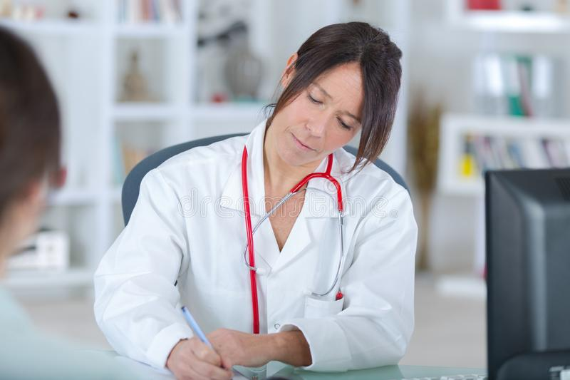 Beautiful female medicine doctor writing prescription stock photography