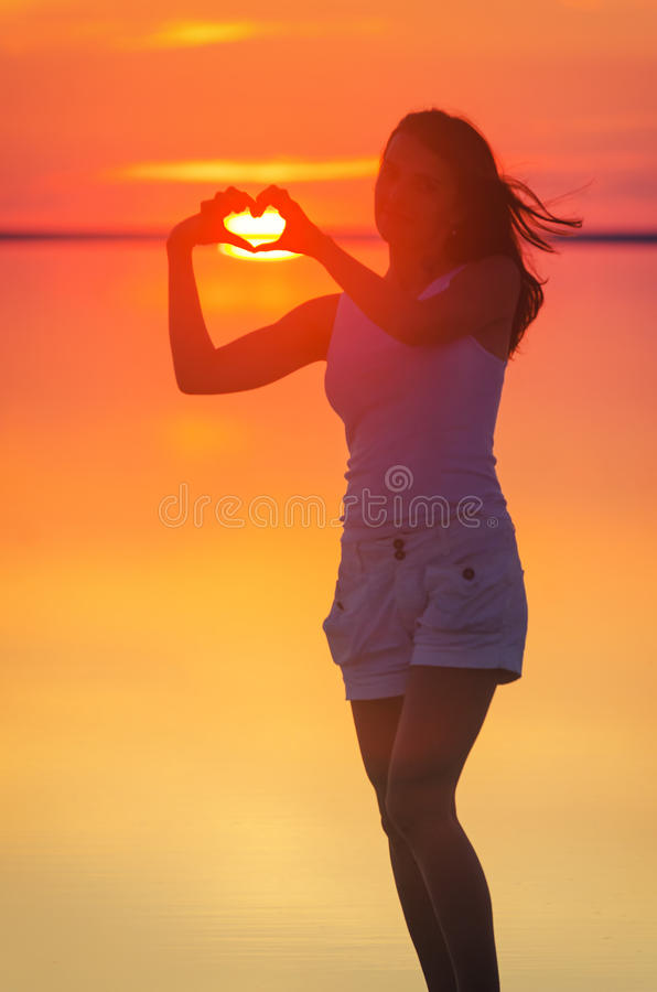 Beautiful female model enjoying sunset and making heart sign on sun. Calm water of salt lake Elton reflects woman`s silhouette. Gi. Beautiful female model stock photography