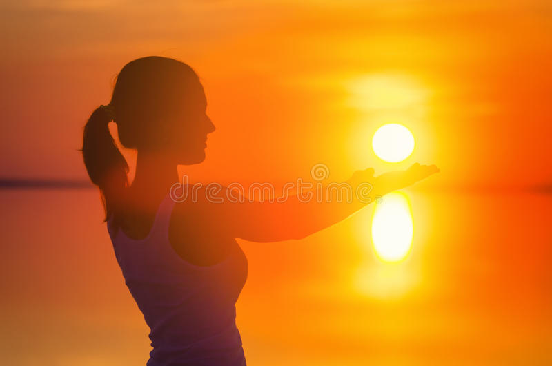 Beautiful female model enjoying sunset and touch sun at seaside. Calm water of salt lake Elton reflects woman`s silhouette. Girl stock photography