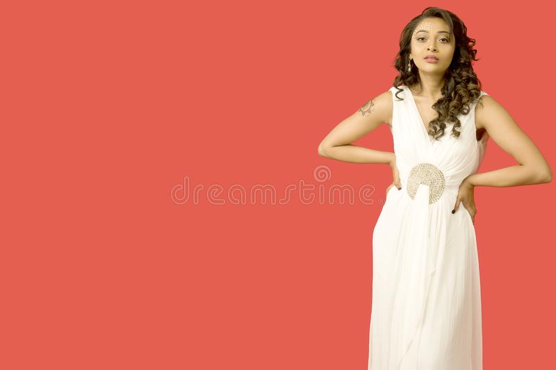 Beautiful female model in a flowy white gown in front of a solid red background royalty free stock images