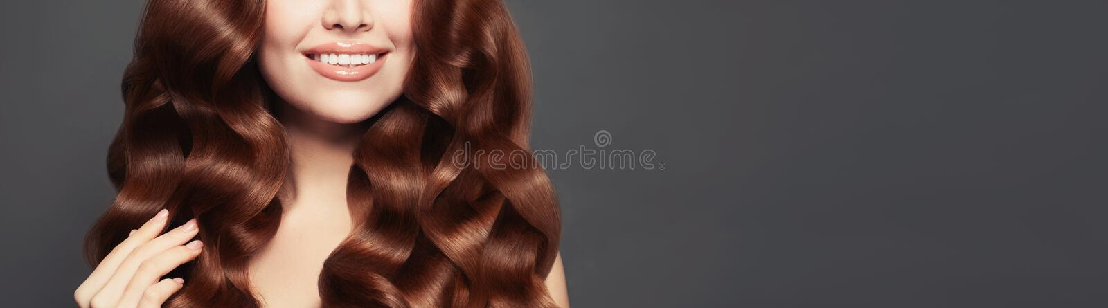 Beautiful female model hair. Long curly healthy hair and perfect smile royalty free stock photo