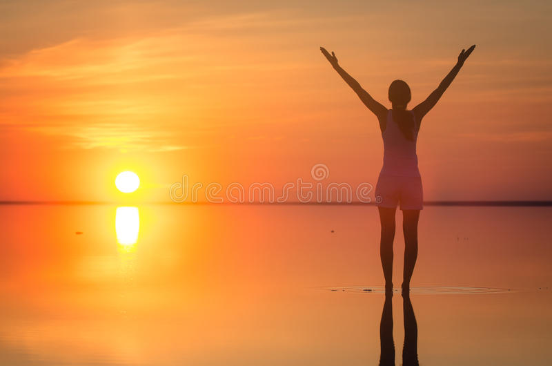 Beautiful female model open arms under sunrise at seaside. Calm water of salt lake Elton reflects woman silhouette. Sun goes royalty free stock image