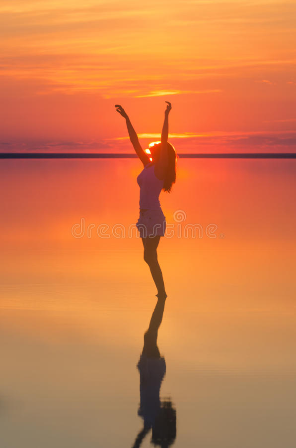 Beautiful female model open arms under sunset at seaside. Calm water of salt lake Elton reflects woman silhouette. Sun goes behind. Beautiful female model open stock image