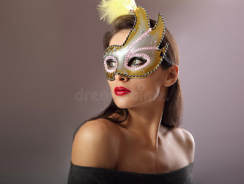 Beautiful female model posing in carnival mask with bright makeup and red lipstick on empty copy space background. Closeup royalty free stock image