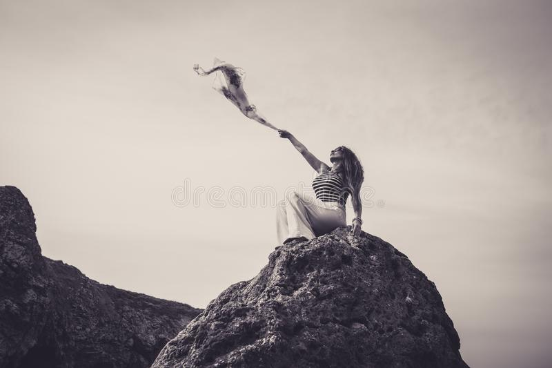 Beautiful woman sat on top of cliff holding scarf to wind stock photo