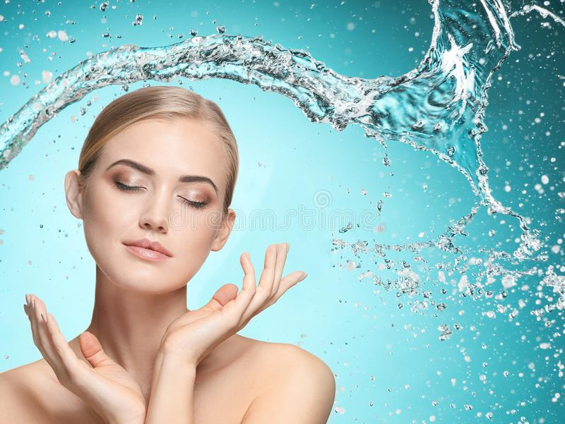 Beautiful female model with splashes of water in her hands. Beautiful woman with splashes of water in her hands. Beautiful girl under splash of water with fresh royalty free stock image
