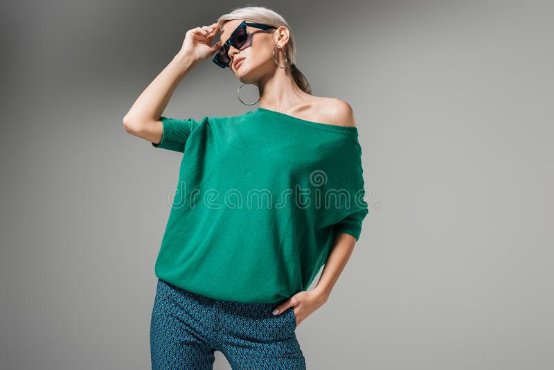 Beautiful female model in sunglasses and green sweater posing. Isolated on grey background stock images