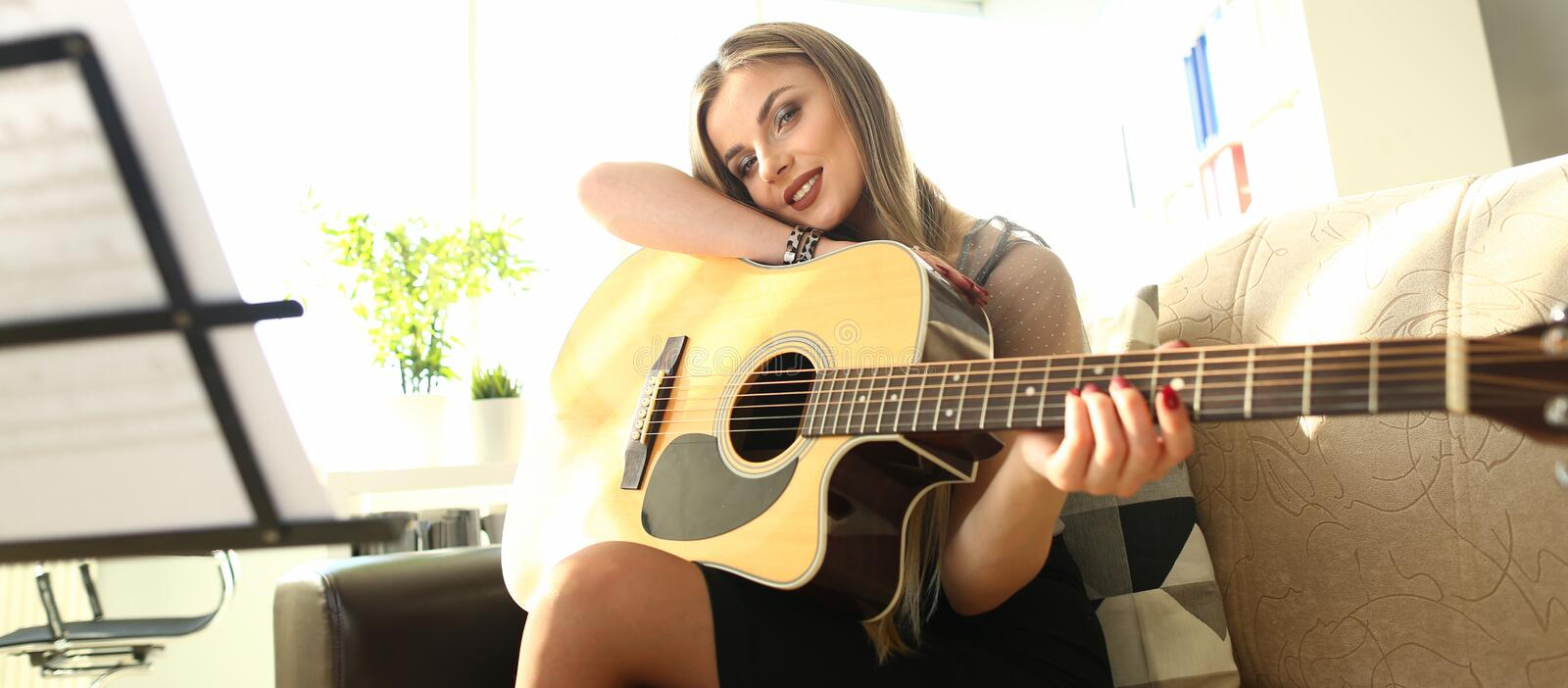 Beautiful Female Musician Art Inspiration Concept. Caucasian Girl at House Lesson. Beautiful Woman Composing Melody Playing Chords on Acoustic Guitar. Musical royalty free stock photography