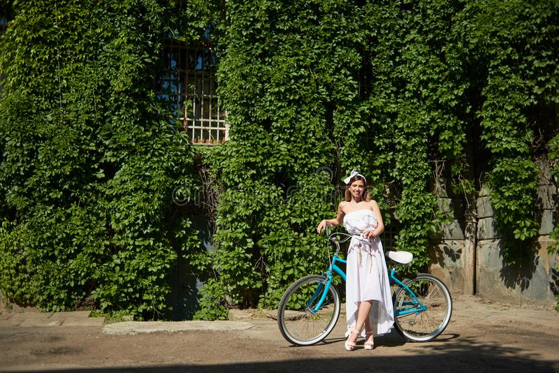 Beautiful female near tuquoise bike in front of ivy tree wall stock photography