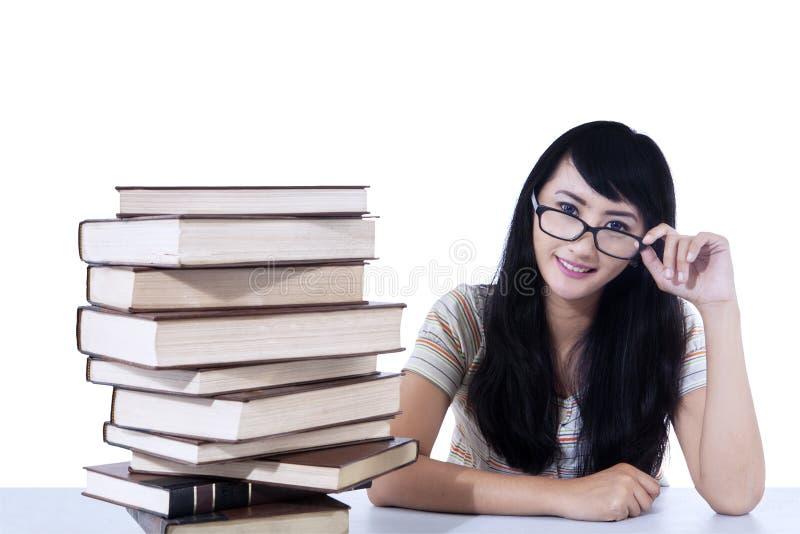 Beautiful female nerd student and books - isolated stock image
