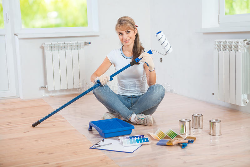 Beautiful female painter sitting on wooden floor with paint too. Ls and holding paintroller and looking at camera stock images