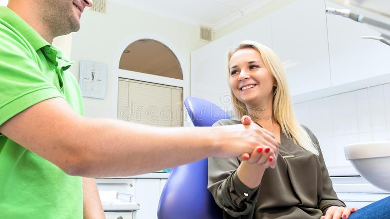 Portrait of beautiful female patient sitting in dentist chair and shaking hands with doctor stock image