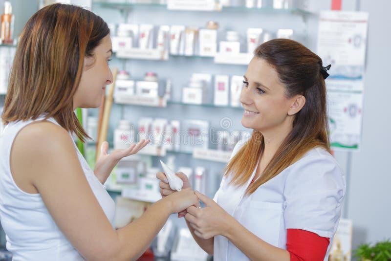 Beautiful female pharmacist helping customer at drugstore stock photos