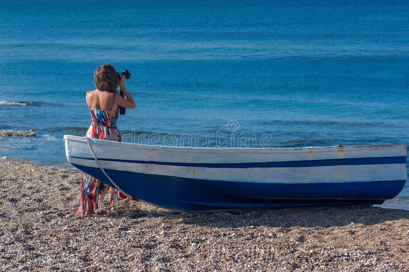 Beautiful female photographer in the dress with professional camera near boat on the sand royalty free stock photography