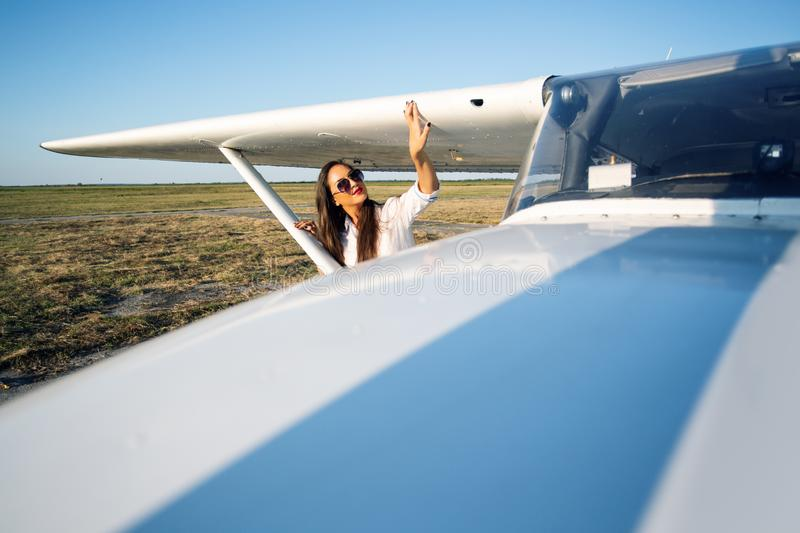 Female pilot in sunglasses with modern small aircraft in background royalty free stock photo