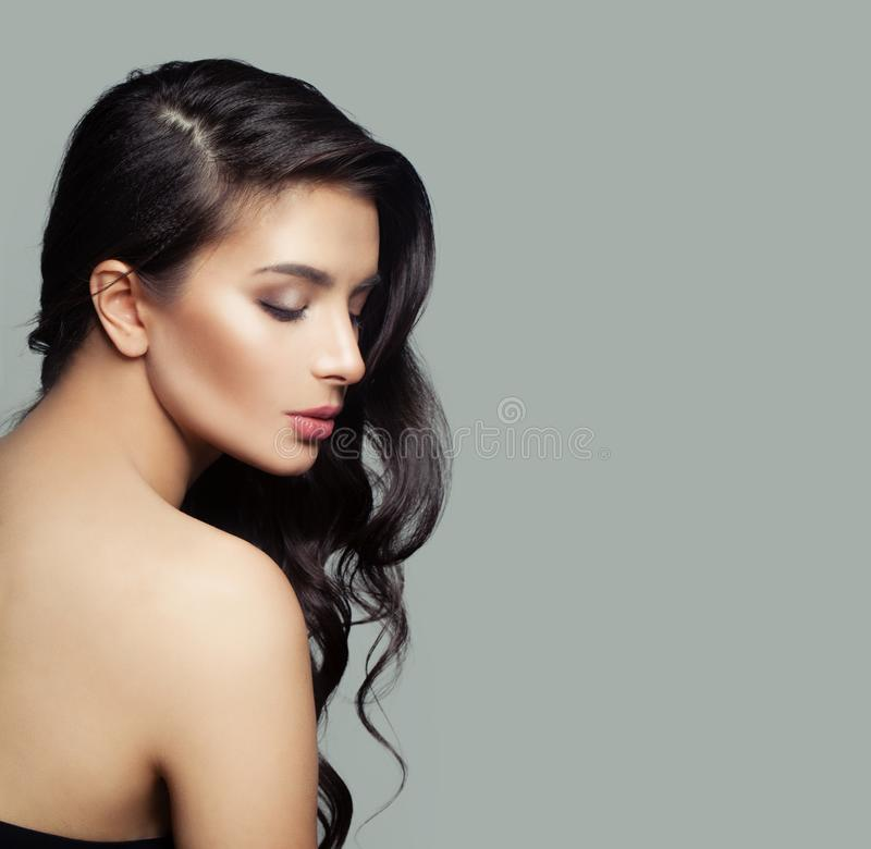 Beautiful female profile. Cute brunette woman with natural makeup and long black hair on gray background stock photos