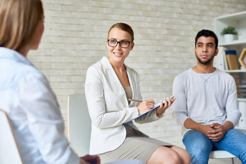 Beautiful Female Psychologist Leading Group Therapy Session. Portrait of beautiful female psychiatrist wearing glasses taking notes on clipboard while talking royalty free stock photo