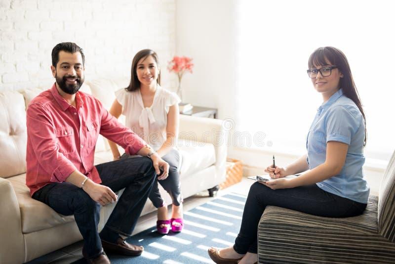 Beautiful female psychotherapist with hispanic couple royalty free stock photography